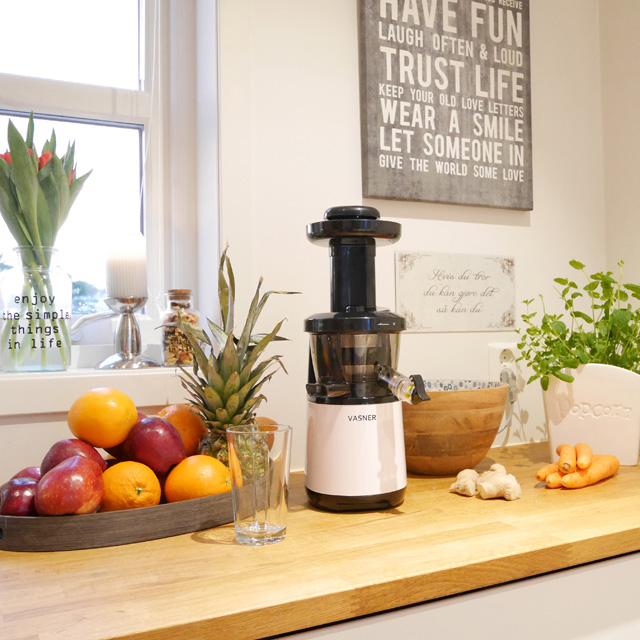 VASNER's cold press juicer Juica on the counter surrounded by fruits and veggies